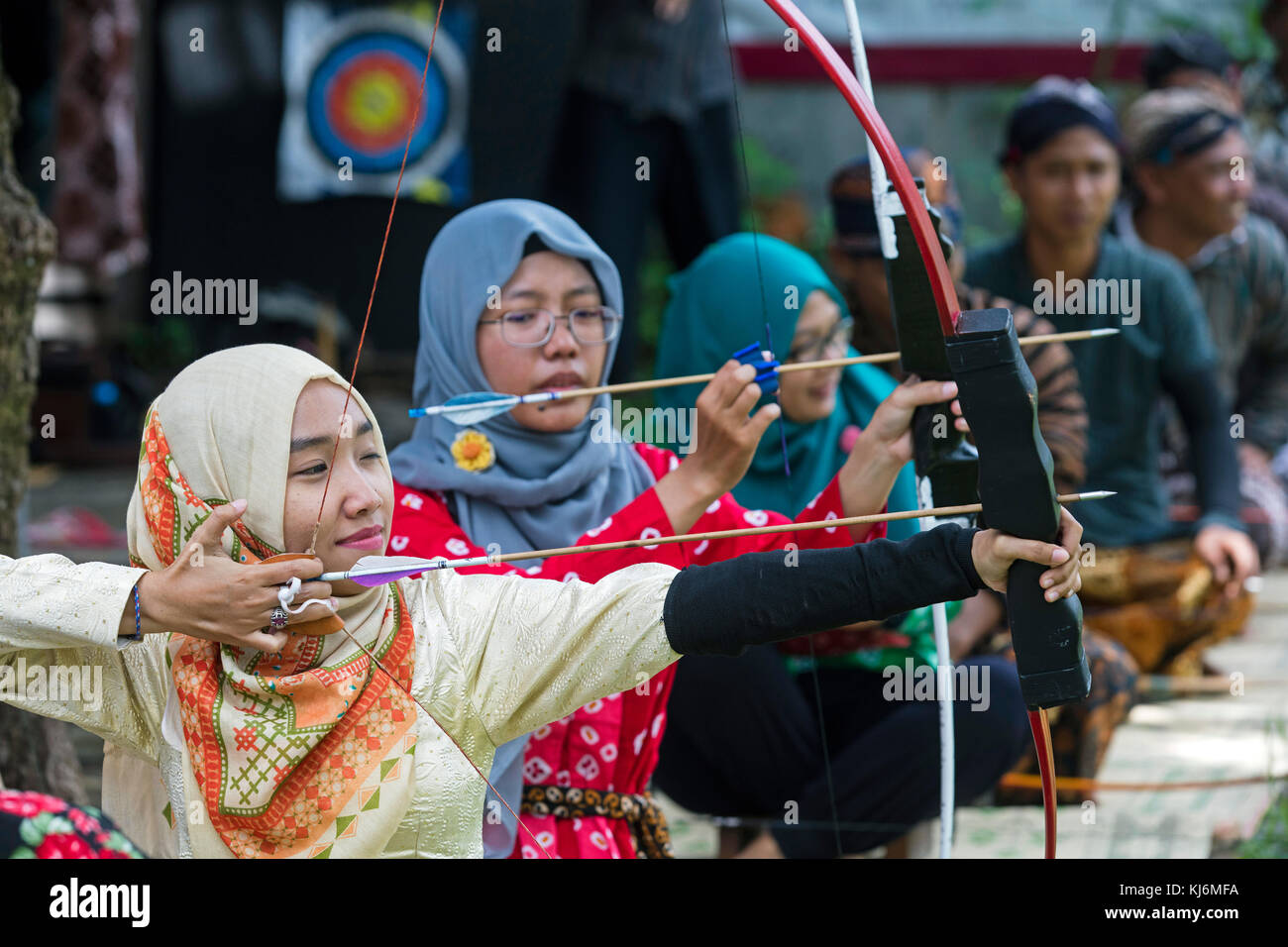 Indonesian girls practicing Jemparingan / traditional Javanese archery by shooting bow and arrows in the city Yogyakarta, - Stock Image