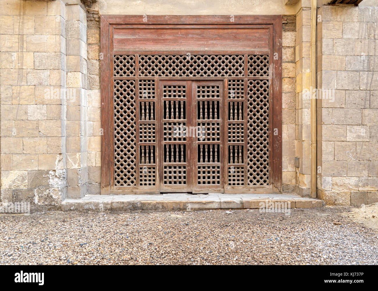 Wooden ornate door over stone brick wall, Old Cairo, Egypt - Stock Image