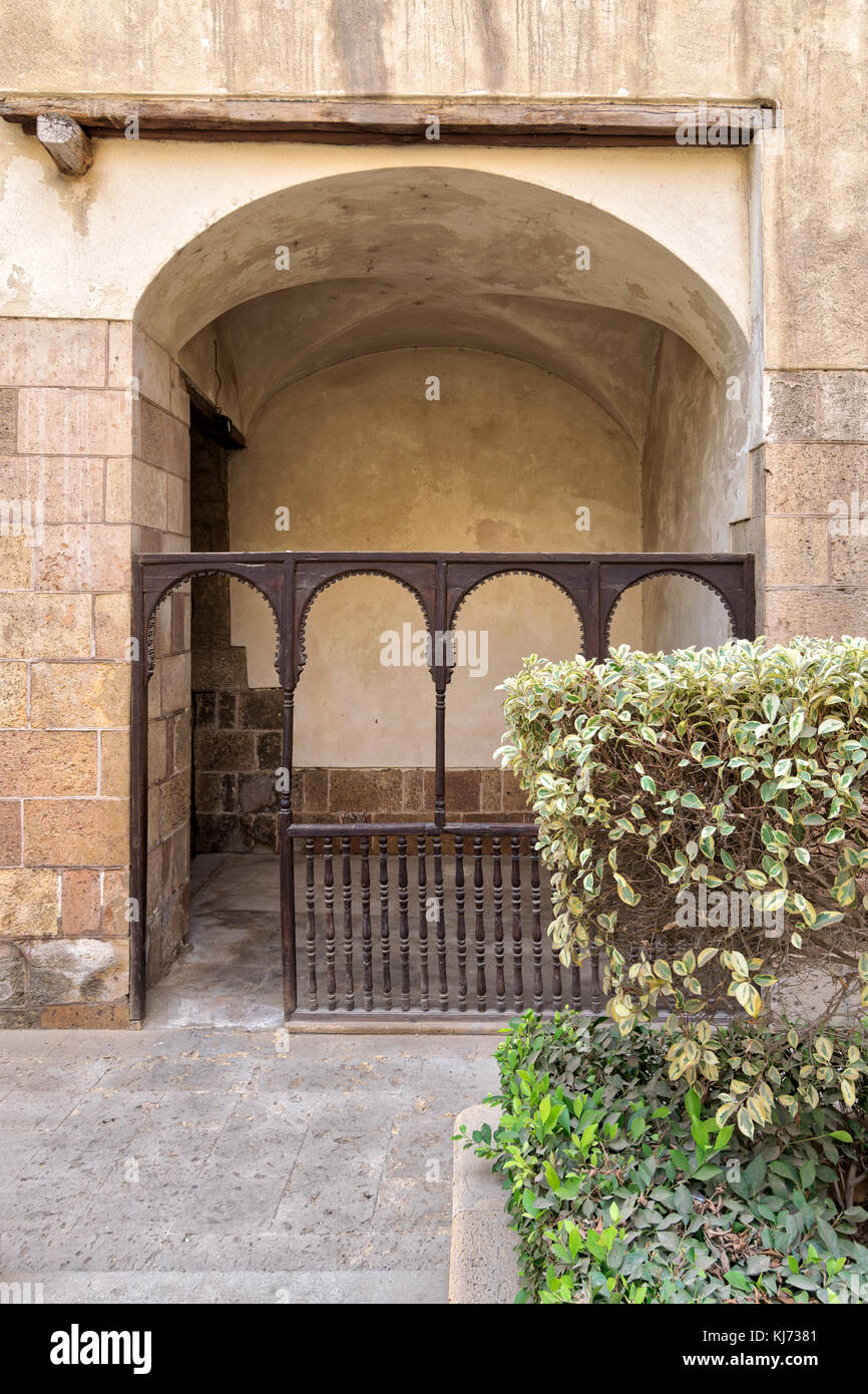 Embedded space with wooden balustrade and wooden arches behind a planted flower box at the external wall of an old - Stock Image