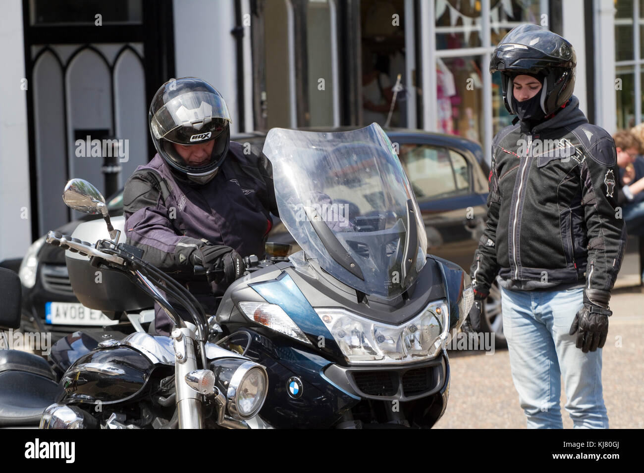 Couple parking a large motorbike on a sunny day - Stock Image