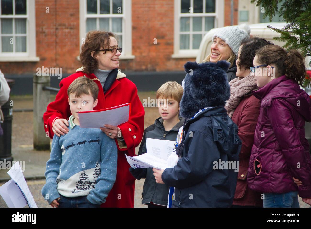Women and children sing Christmas carols - Stock Image