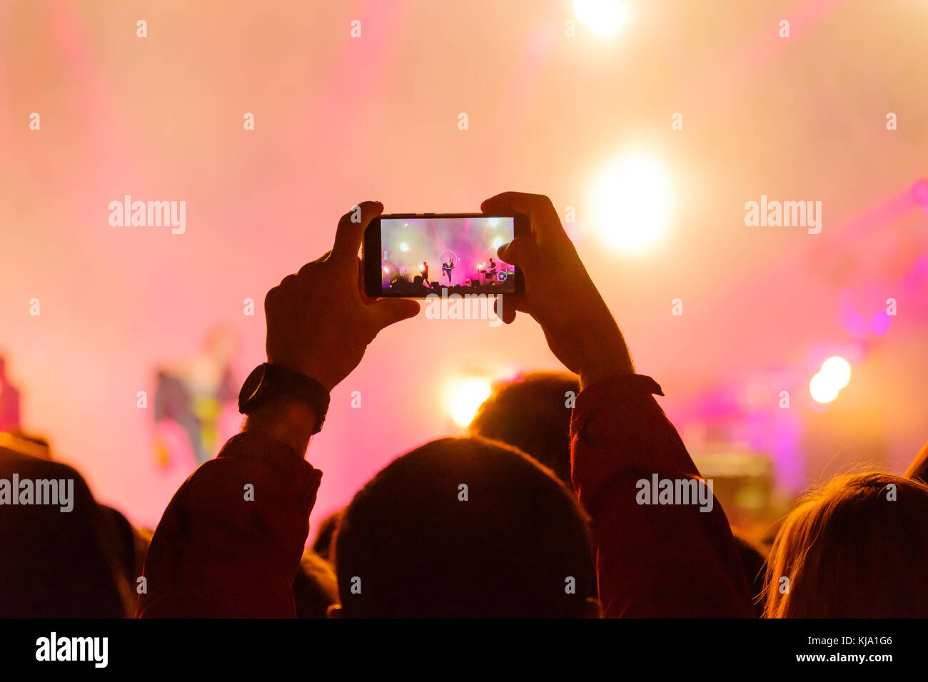 Concert visitor shoots video - Stock Image