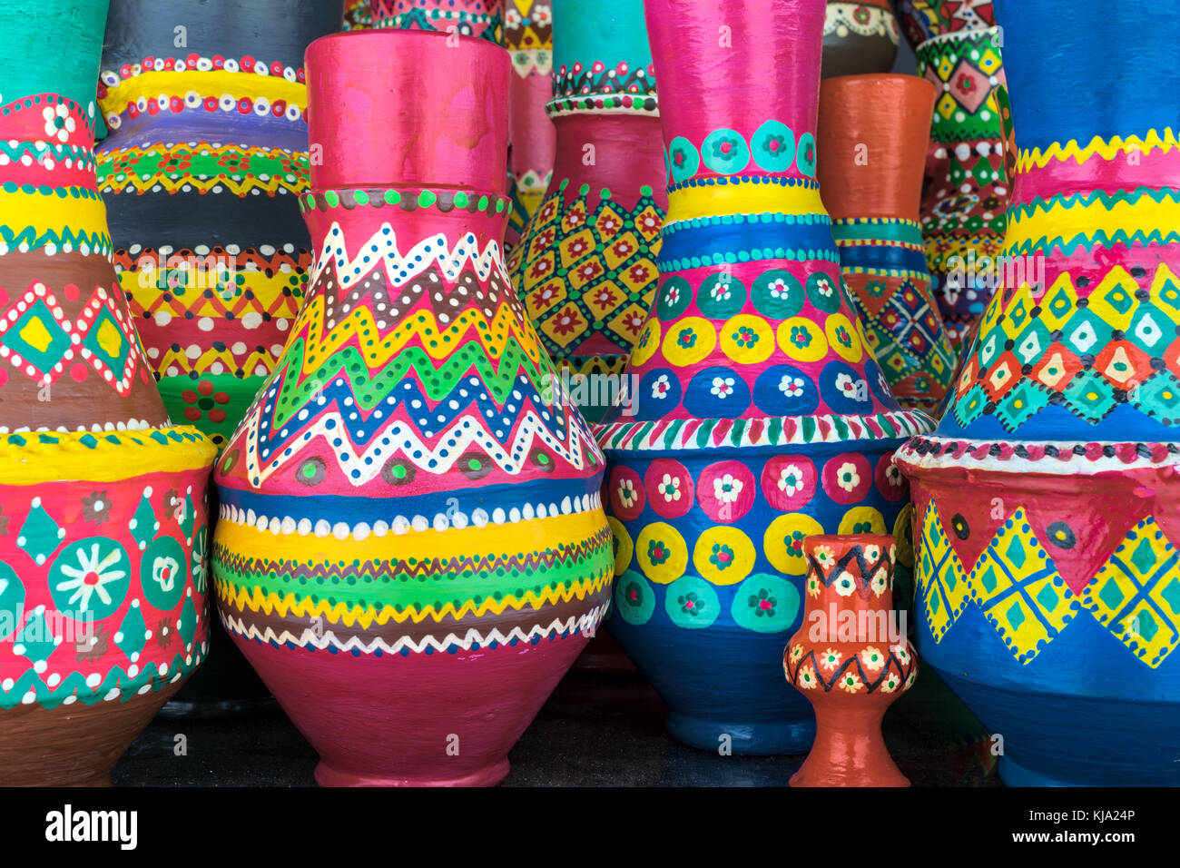 Front view of a composition of artistic painted colorful handcrafted pottery vases - Stock Image