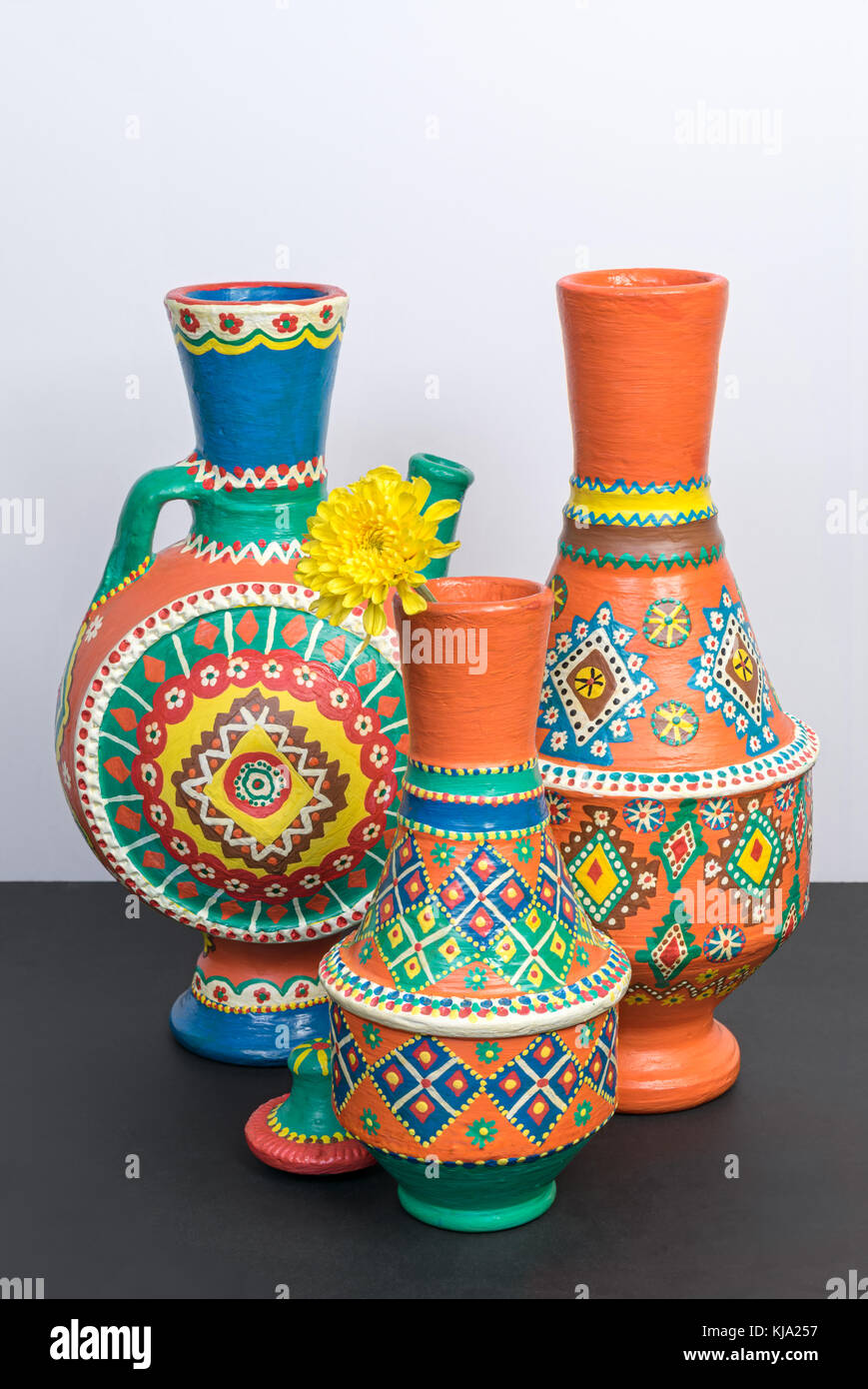 Studio shot of still life of three orange ornate pottery vases on background of black table and white wall - Stock Image