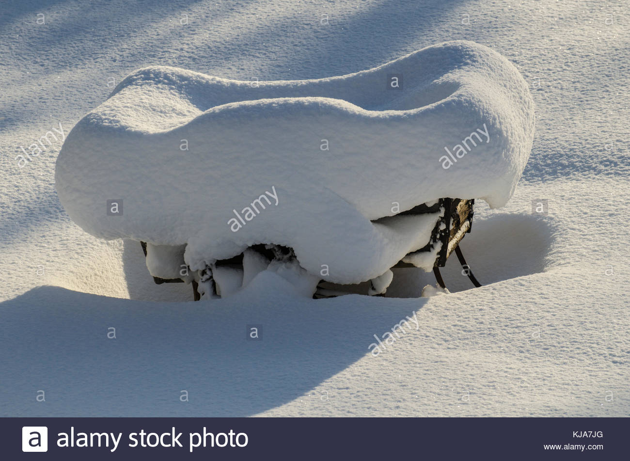 A freezing cold day and the very old wooden wagon is packed with glittering snow. - Stock Image