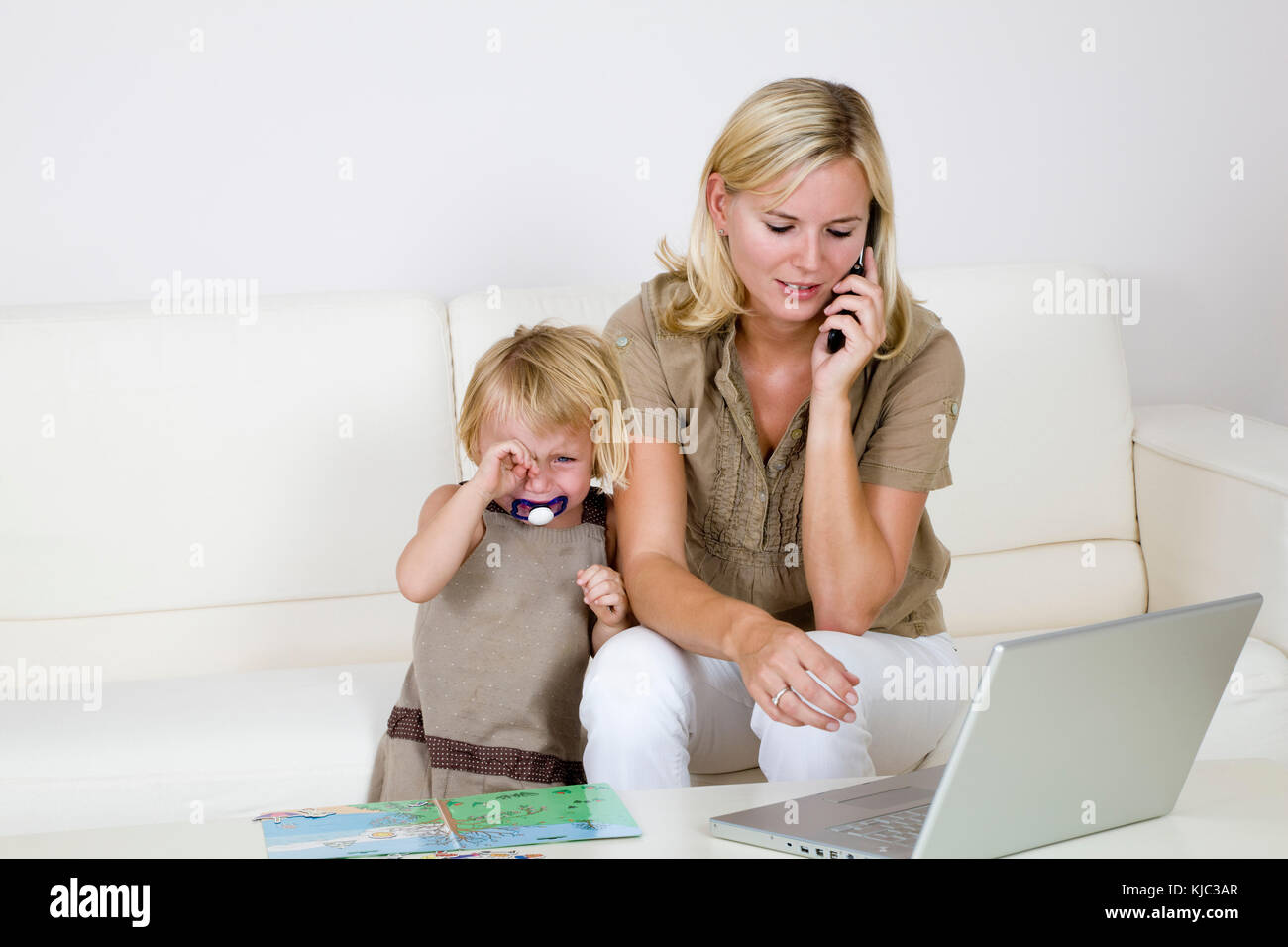 Mother Using Laptop and Cell Phone, Toddler Standing Beside Her Crying - Stock Image