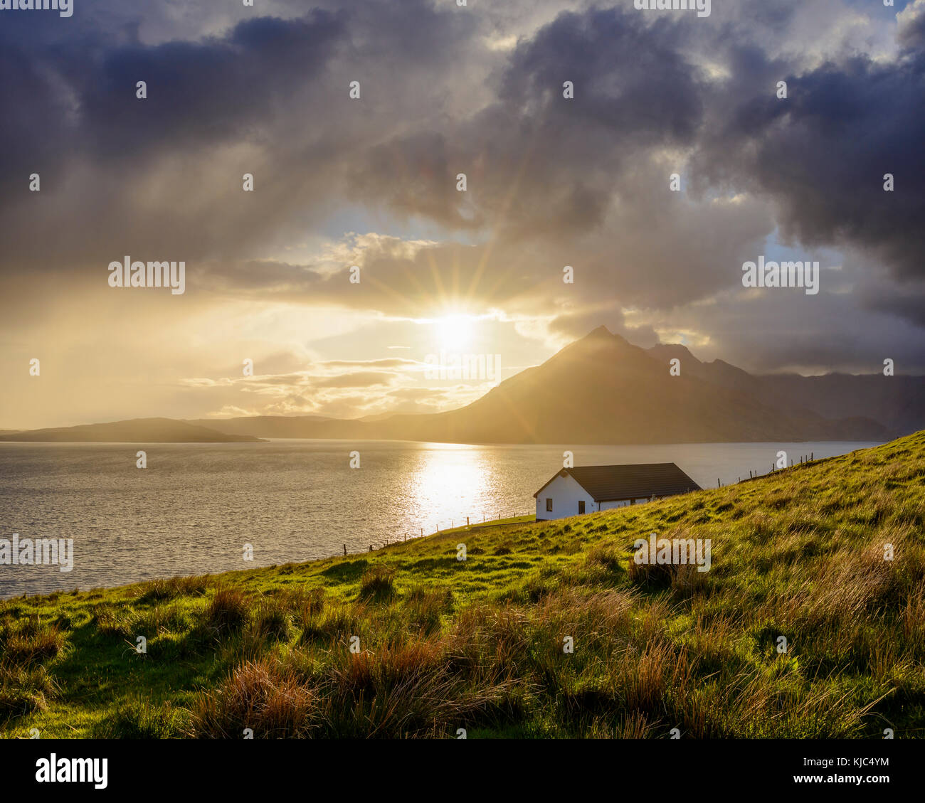 Rooftop of a house along the Scottish coast with sun shining through the clouds over Loch Scavaig, Isle of Skye - Stock Image