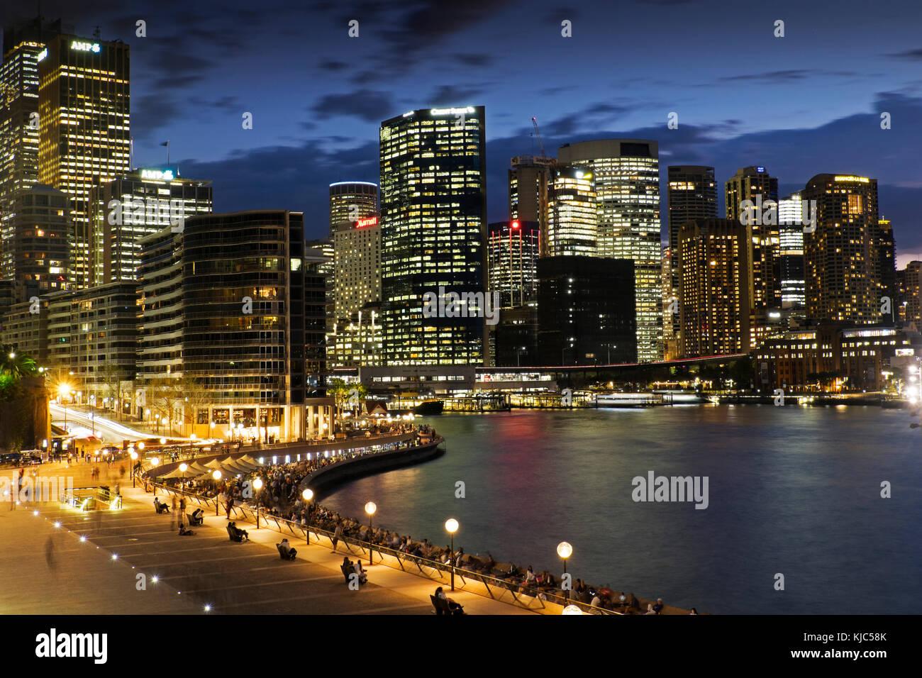 Seaside Promenade at the Circular Quay and Sydney skyline at dusk, Australia - Stock Image