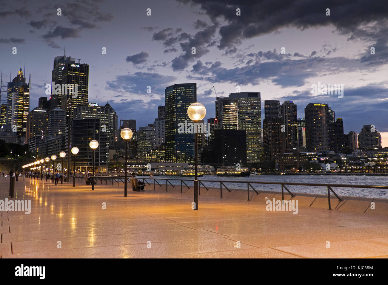 Seaside Promenade and Sydney skyline at dusk at the Circular Quay in Australia - Stock Image