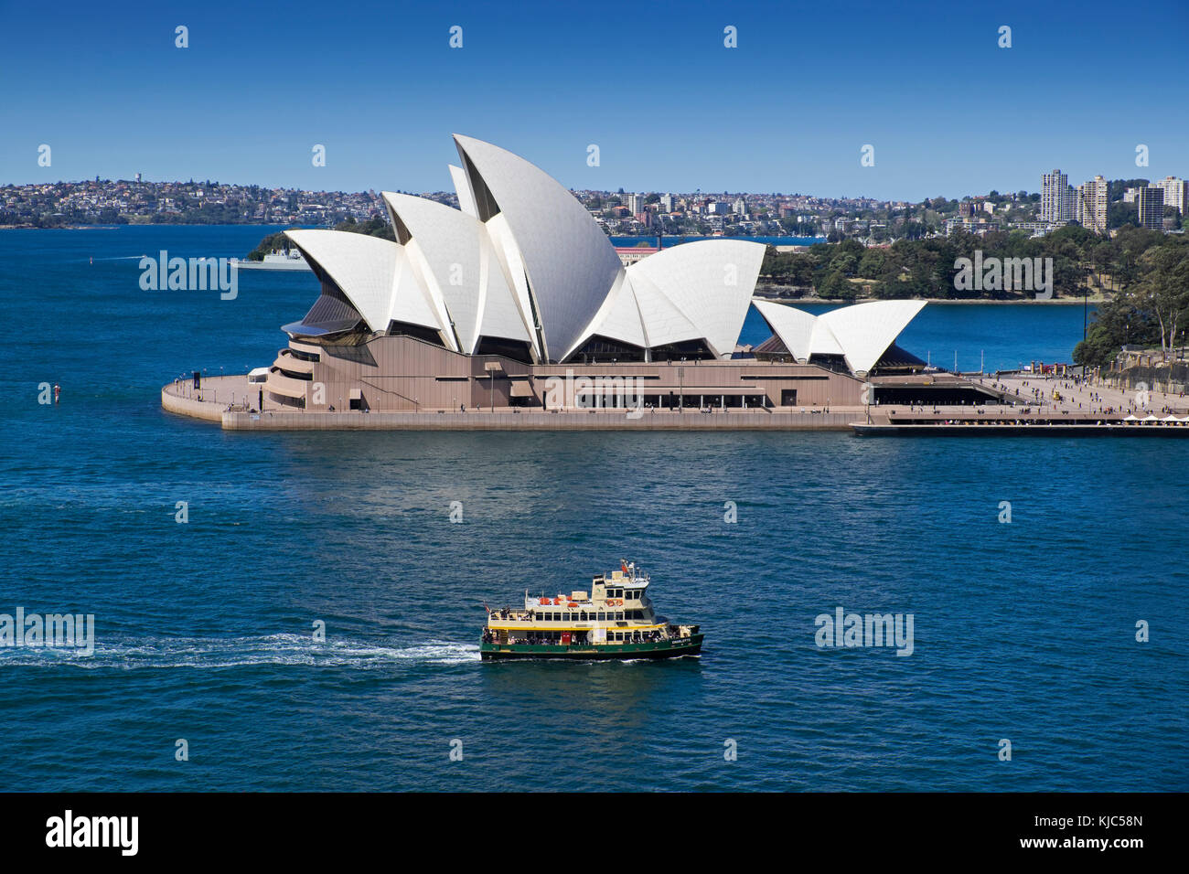 Ferry crossing Sydney Harbour with the Sydney Opera House on a sunny day in Sydney, Australia - Stock Image