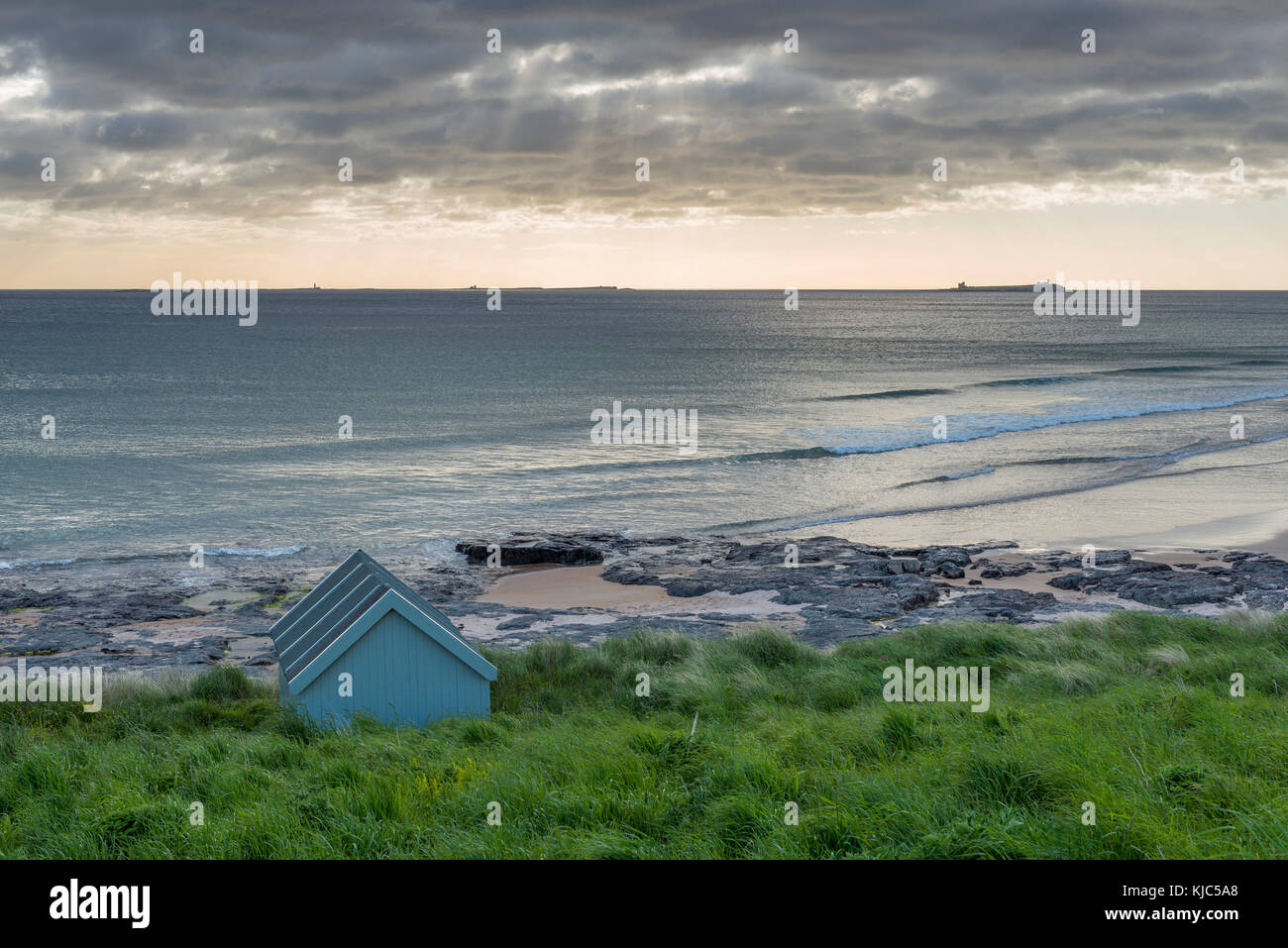 Fisherman's hut on the beach along the North Sea with dramatic cloudy sky at Bamburgh in Northumberland, England, - Stock Image