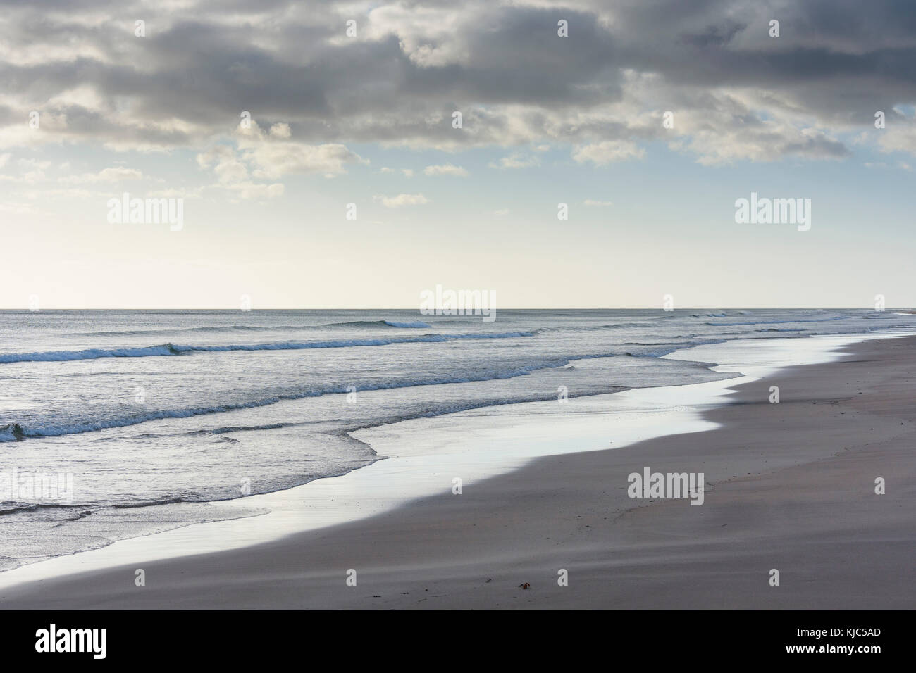 Surf of the North Sea along the beach at Bamburgh in morning light in Northumberland, England, United Kingdom - Stock Image