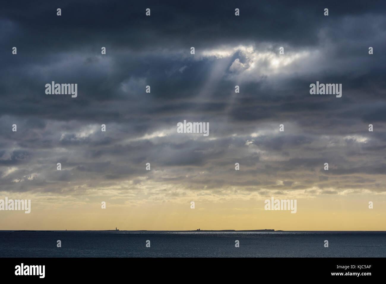 Sun shining through rain clouds over Farne Island in the North Sea at Bamburgh, England, Northumberland - Stock Image
