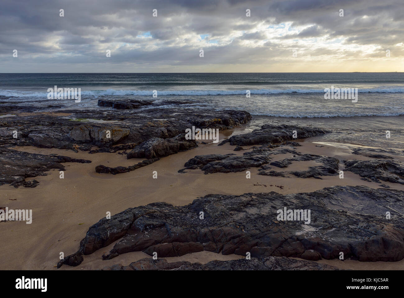 Rocky beach and the surf of the North Sea at Bamburgh in Northumberland, England, United Kingdom - Stock Image