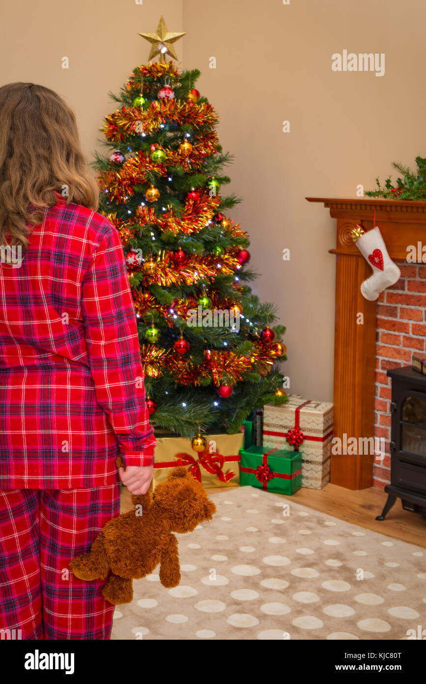A young girl holding a teddy bear on Christmas morning as she discovers that Santa has been and left lots of gift - Stock Image