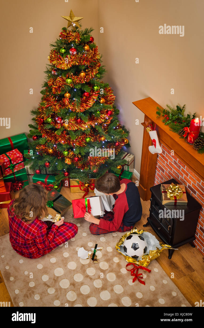 Overhead view of Children opening their gift wrapped presents on Christmas morning sitting next to the tree and - Stock Image