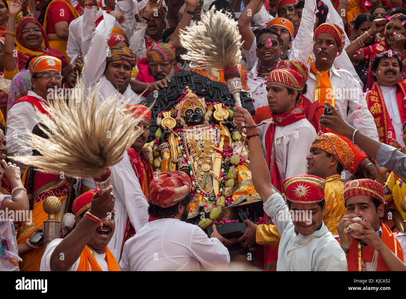 A Black stone image of Vishnu as Jagannath, Loard of the Universe is carried down the steps of the Jagdish Temple - Stock Image