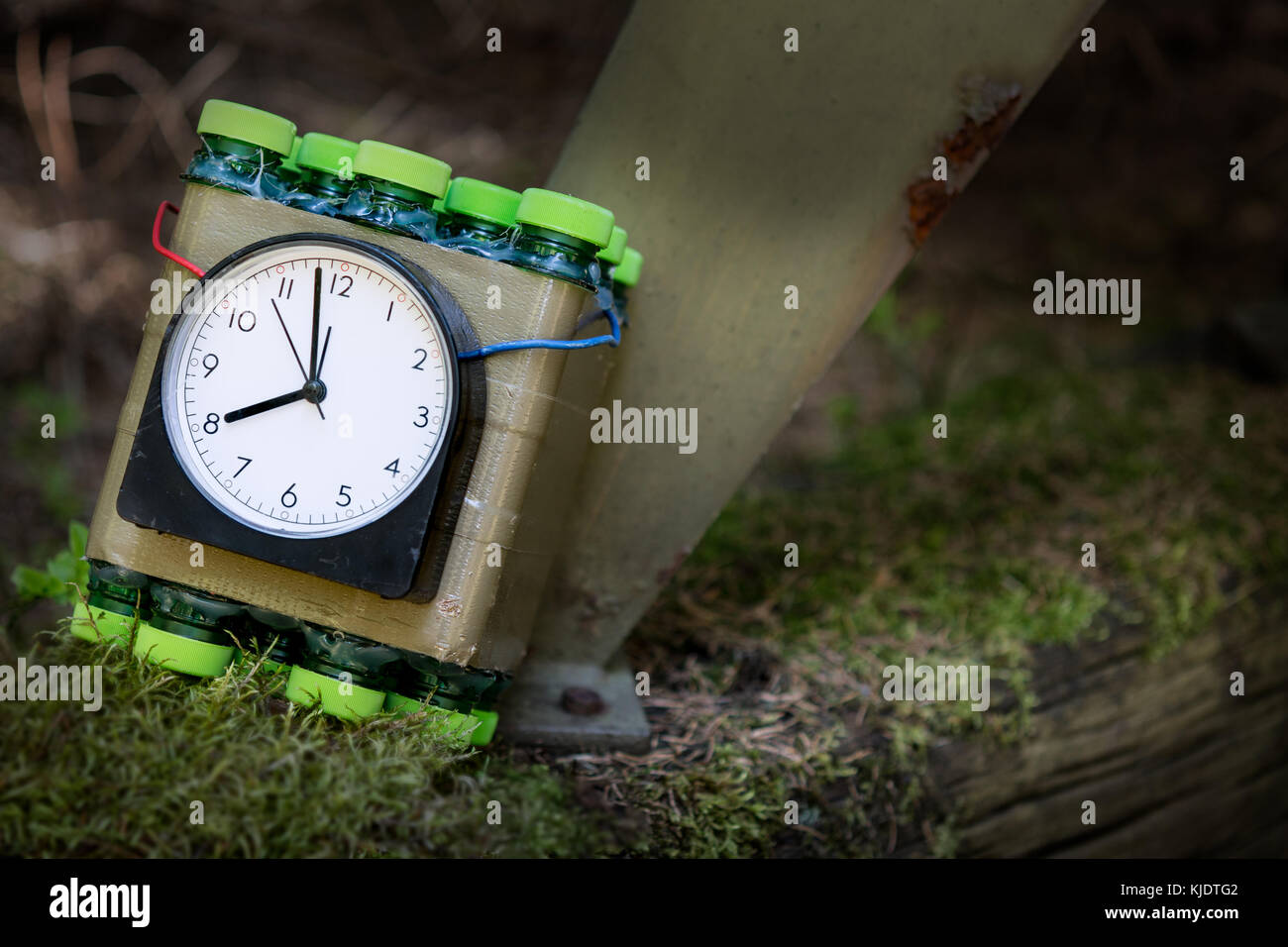 Imitation of timed bomb. Terrorist attack concept. Dangerous explosive placed at metal construction. Small depth - Stock Image