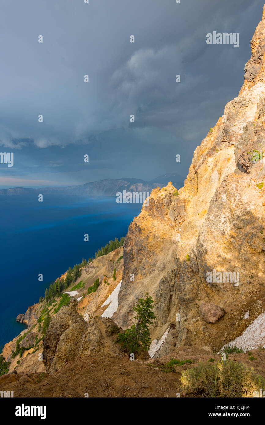 The Sun Highlights Foreground Rocks Before Storm - Stock Image