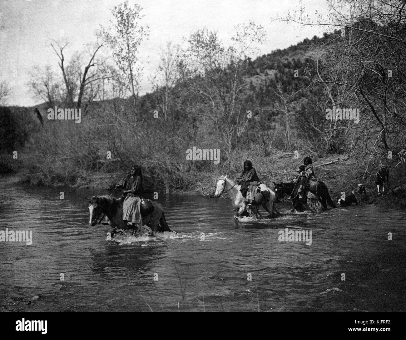 Photograph of a group of Native American women fording (crossing a river at a shallow place) on horseback, titled - Stock Image