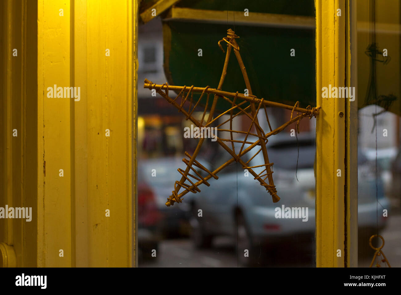 A wooden star hanging in a window for Cristmas - Stock Image