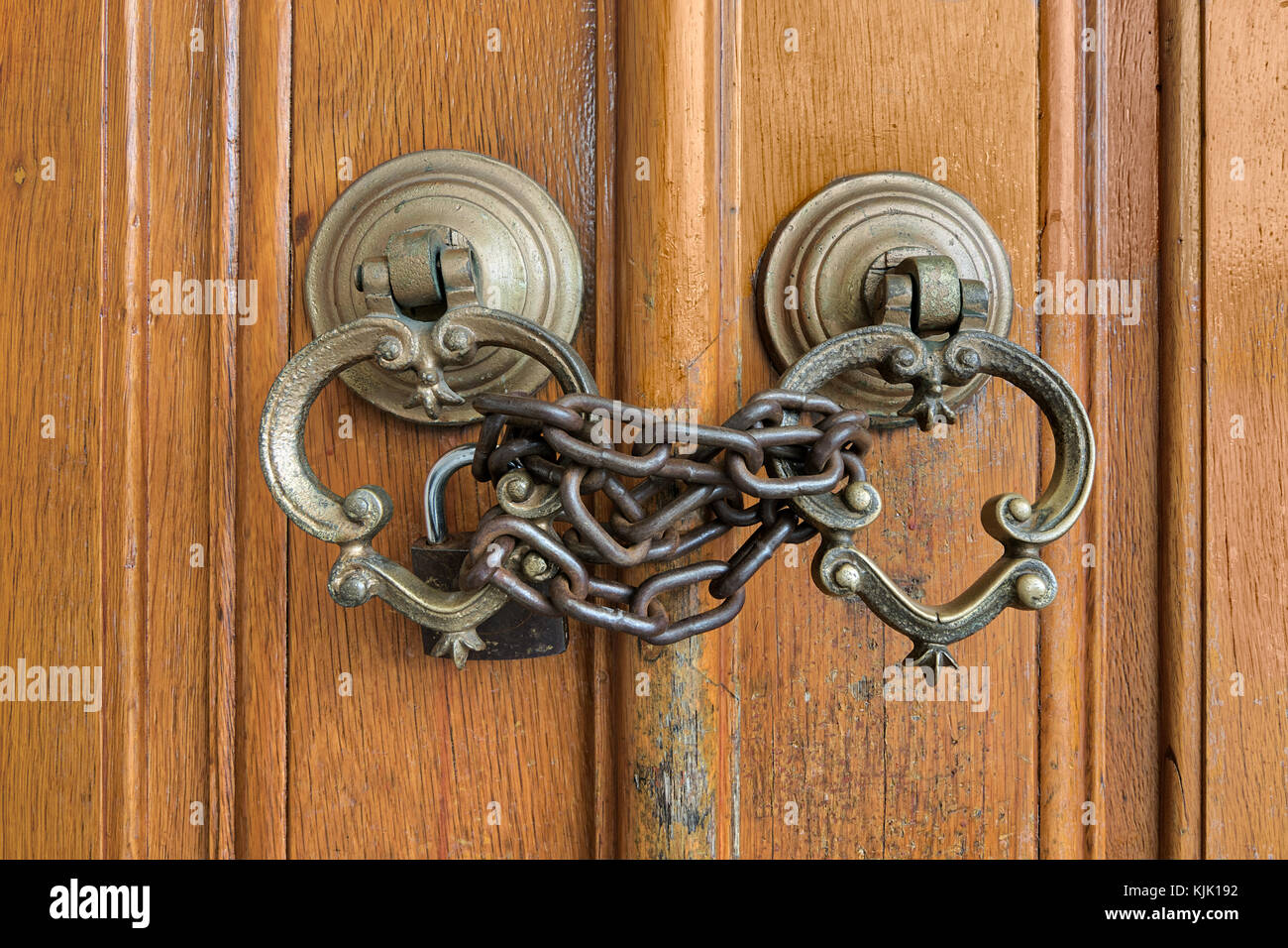 Closeup of two antique copper ornate door knockers over an aged wooden ornate door closed with rusted chain and - Stock Image