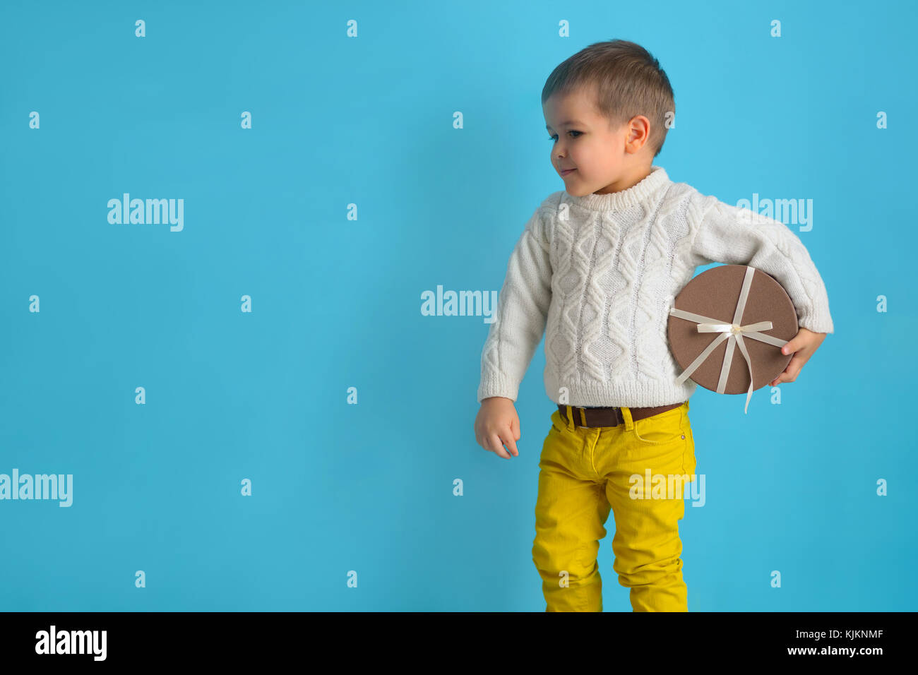 cunning little boy is holding a round gift box with a ribbon. A child in a white sweater on a studio blue background - Stock Image