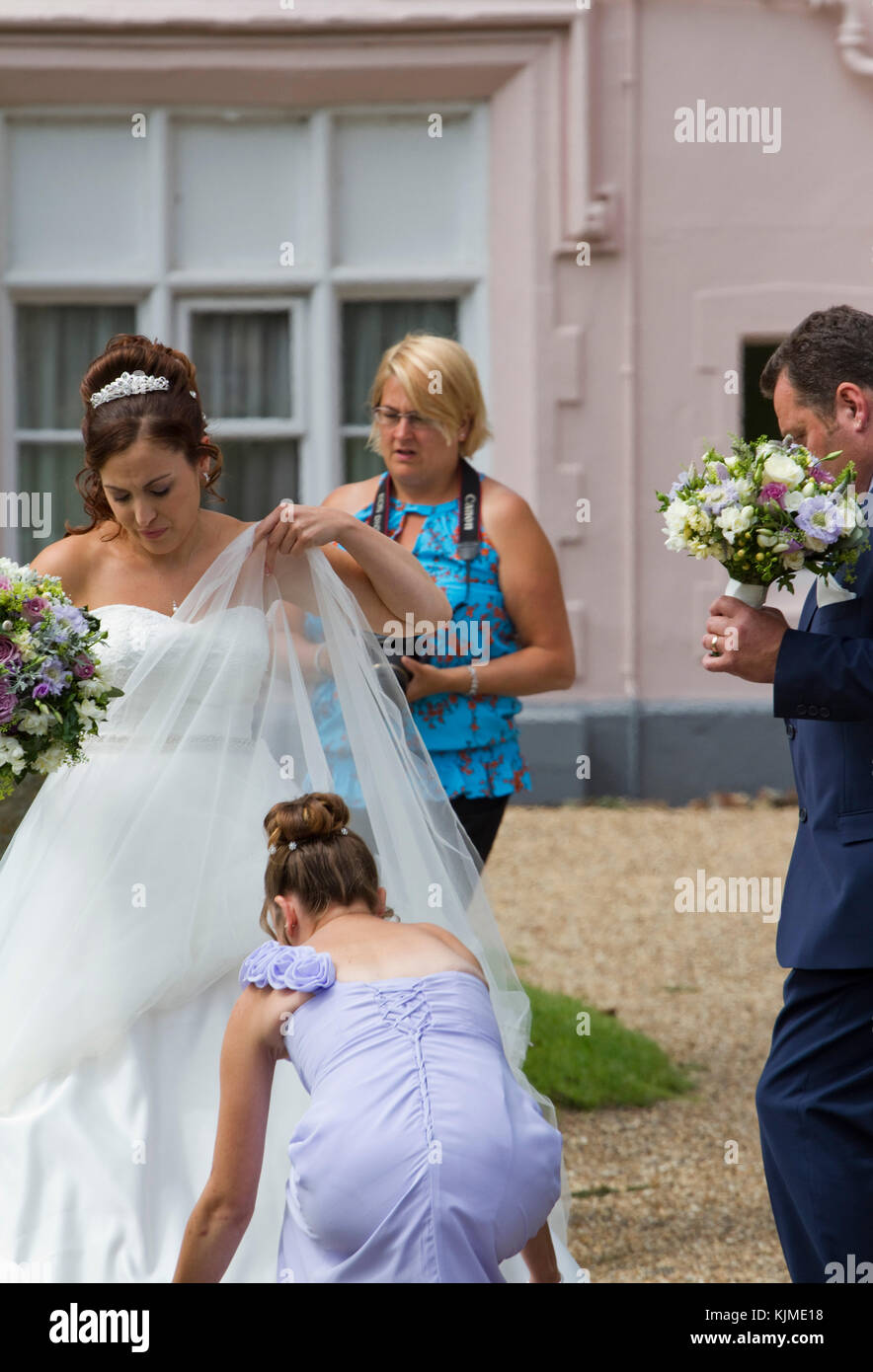 Bride in traditional white with father about to enter church - Stock Image