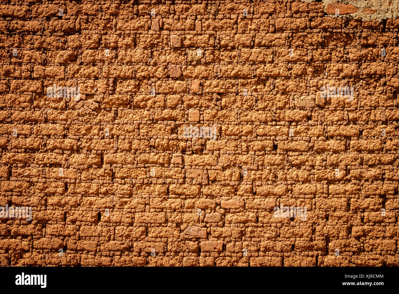 A typical mud brick wall of a house in Uganda. A brick is building material used to make walls, pavements and other - Stock Image
