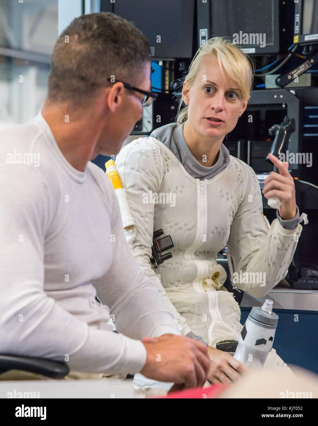 NASA astronauts Mike Hopkins (left) and Kathleen Rubins talk poolside before underwater microgravity spacewalk simulation - Stock Image