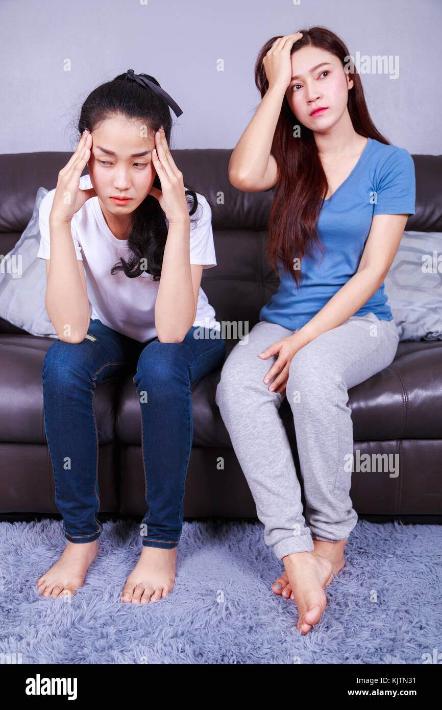 two worried woman on sofa in living room at home Stock Photo