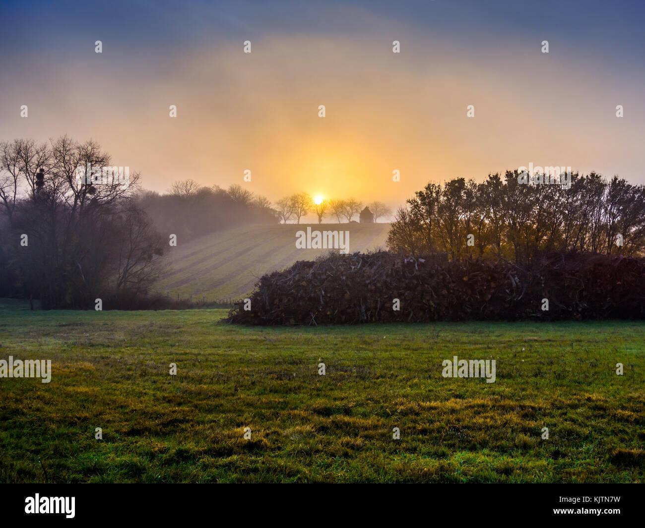 Sunrise through morning mist - France. - Stock Image