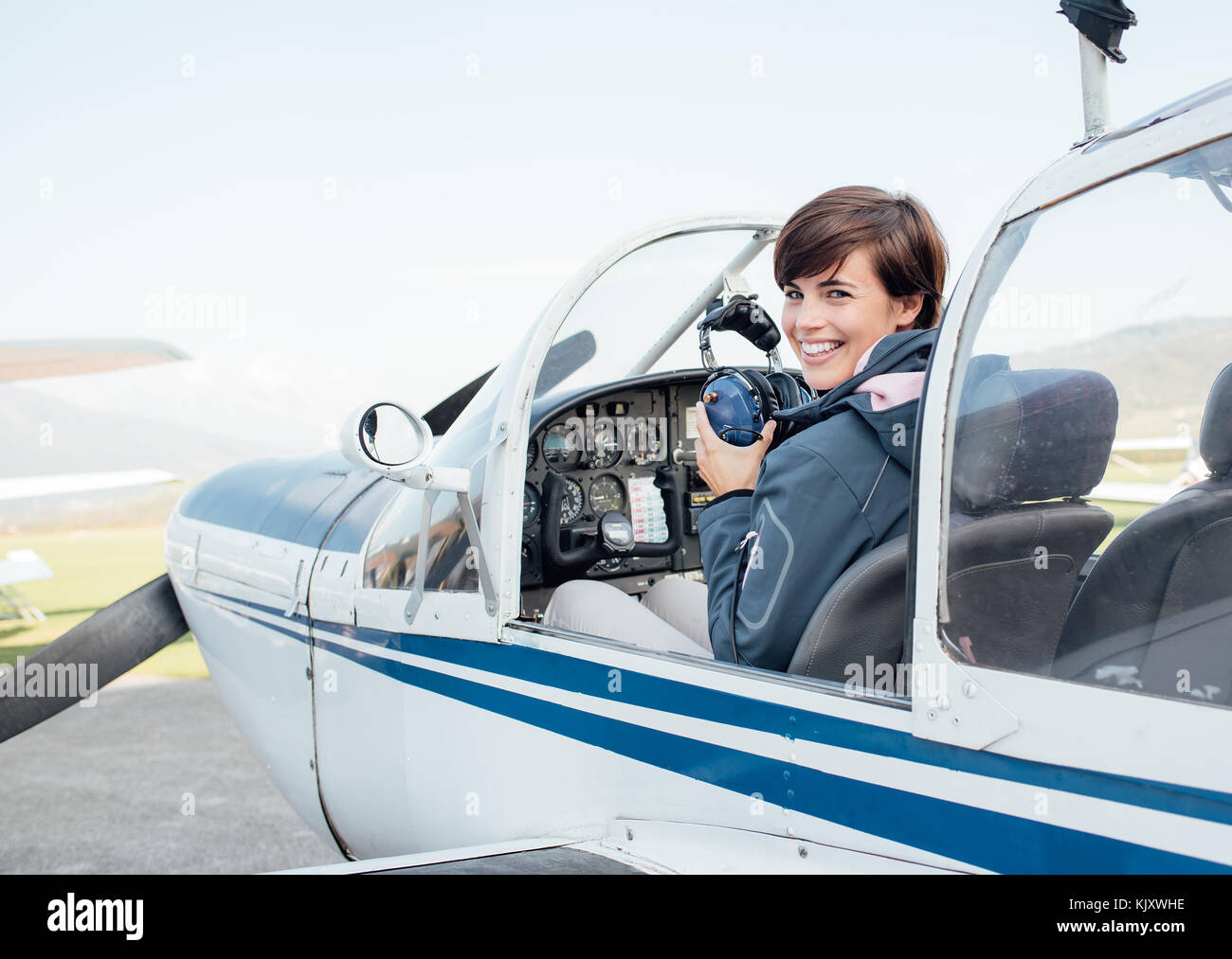 Smiling female pilot in the light aircraft cockpit, she is holding aviator headset and looking at camera - Stock Image