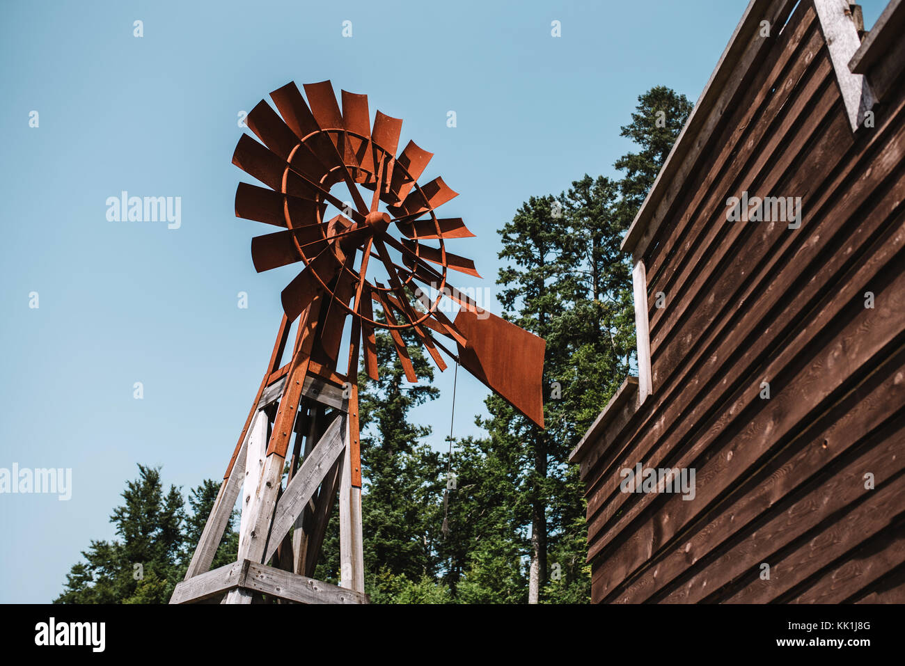 Old rusty windmill with blue sky in background - Stock Image