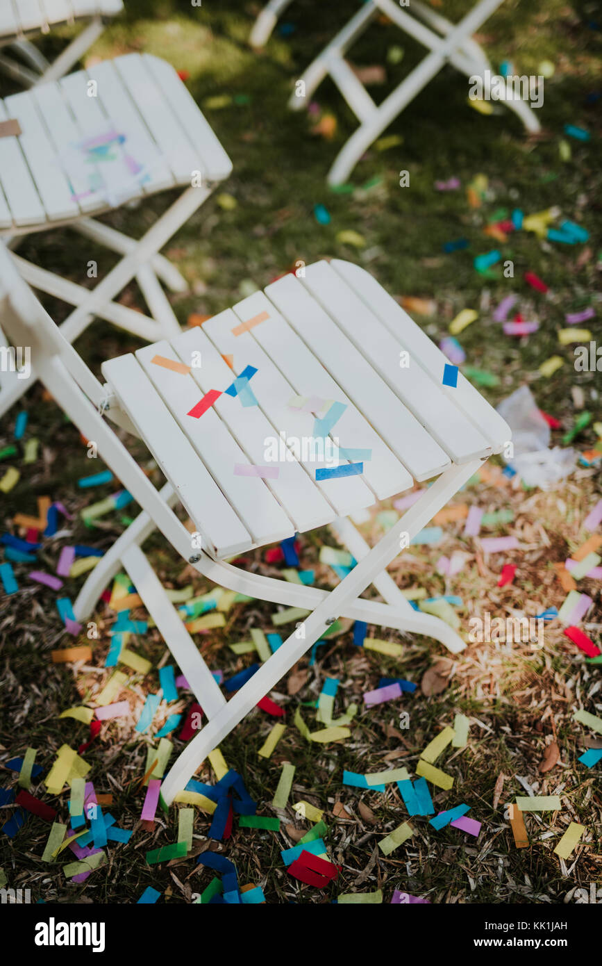 Confetti on white chairs after wedding party - Stock Image