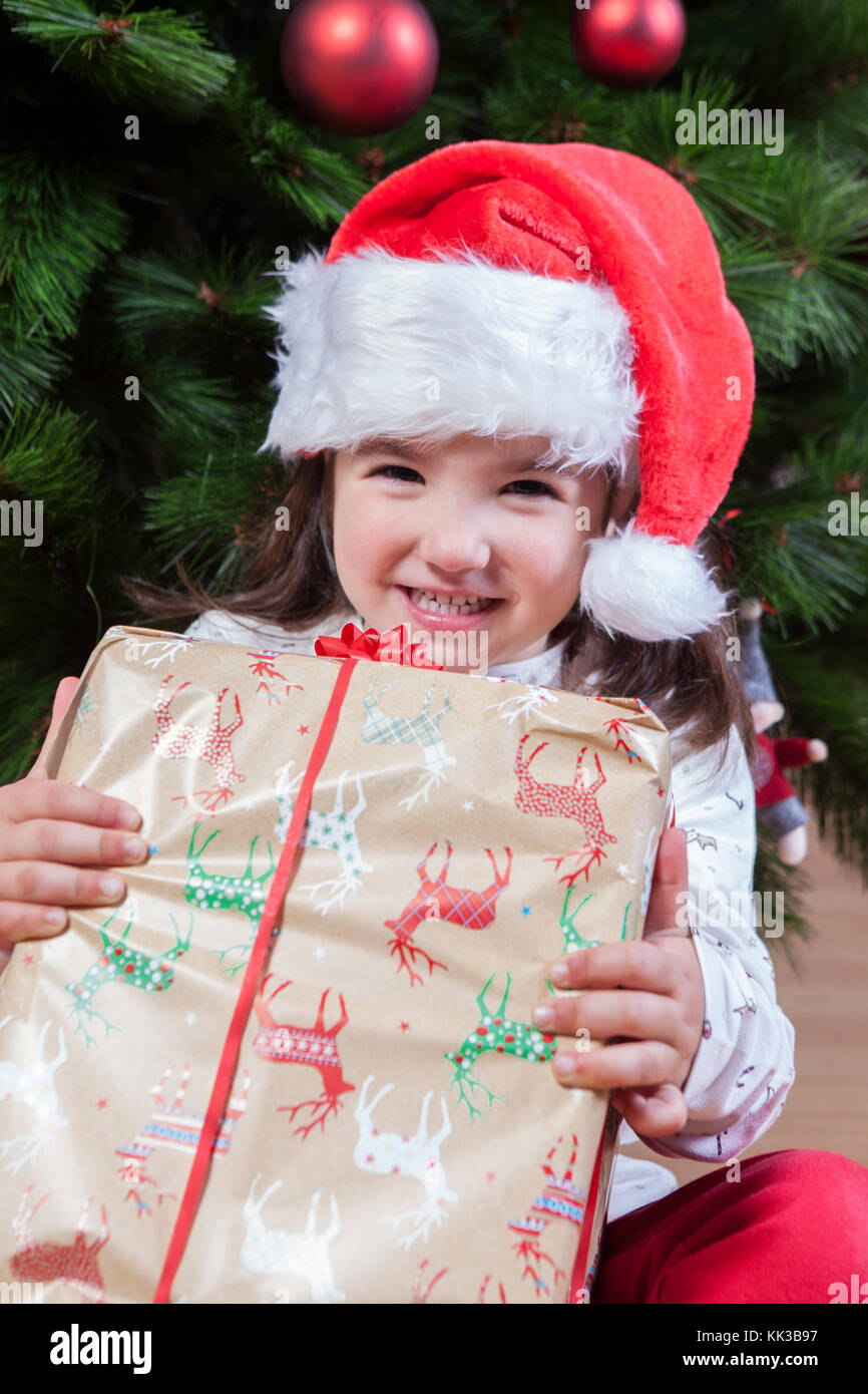 Joyful little girl child with her gift box under Christmas tree. She just have found her present - Stock Image