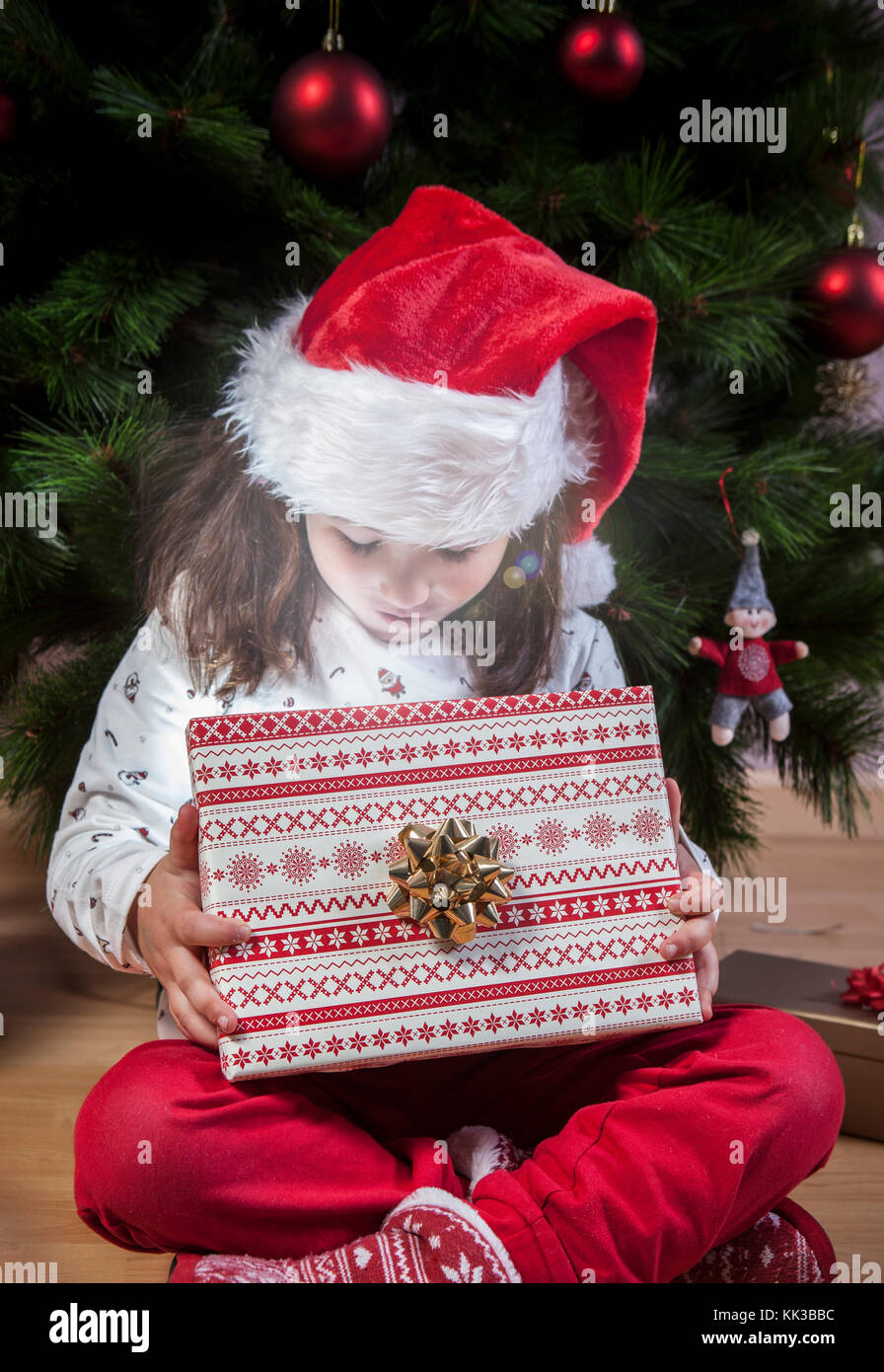 Little girl opening her present beside Christmas tree. She is illuminated by shine from box - Stock Image
