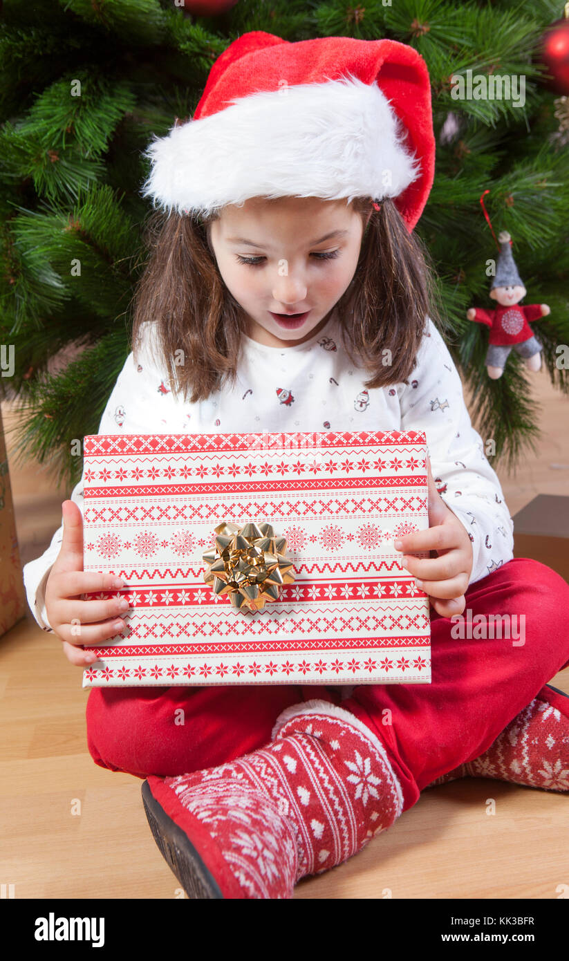 Little girl opening her present under Christmas tree. She is very, very happy - Stock Image