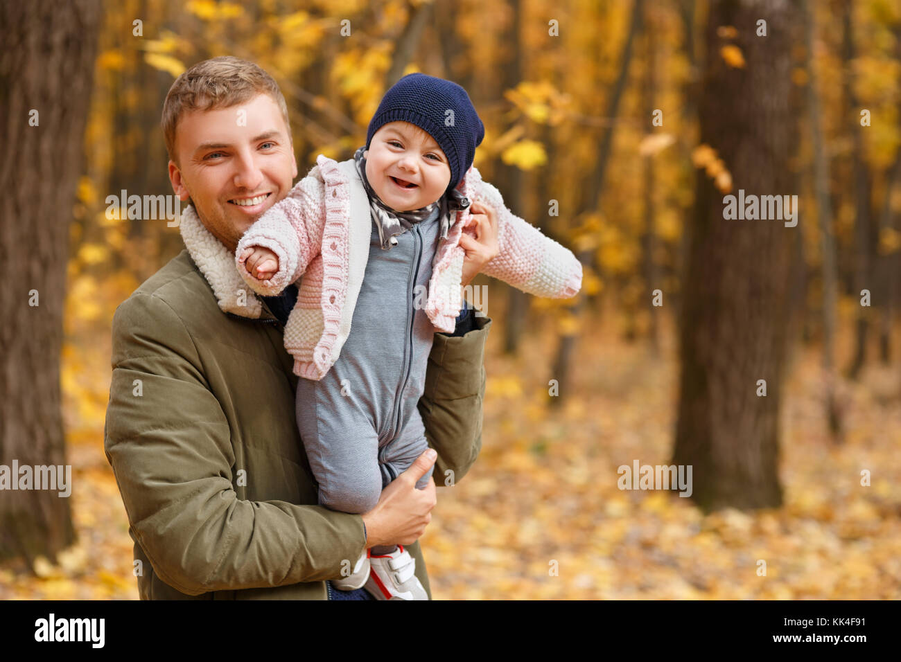 young father play with a little daughter in autumn park. Dad holding baby girl in hands. Happy family, paternal - Stock Image
