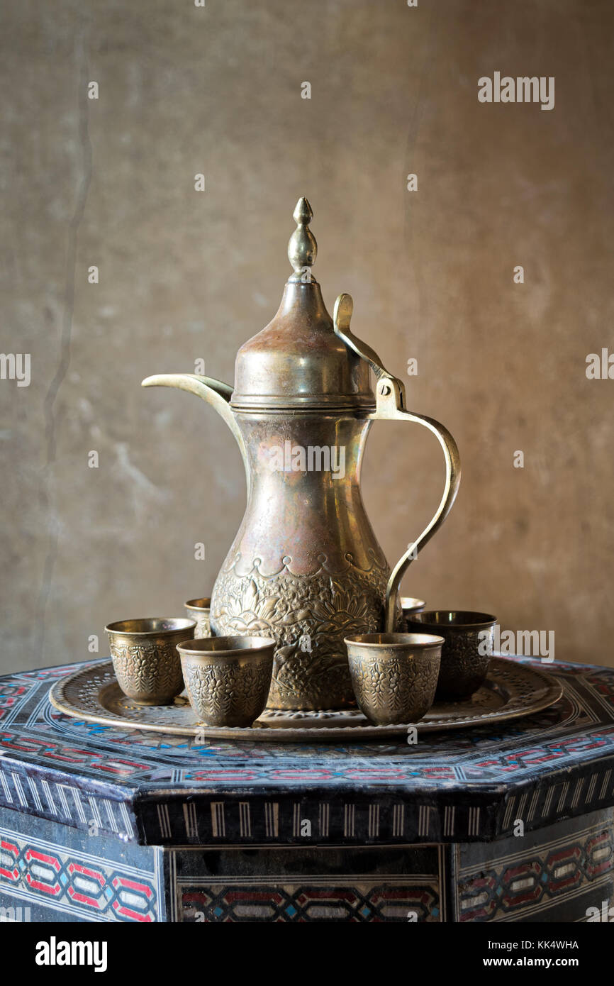 Turkish coffee set: Ottoman ornate coffee pot and small ornate cups on decorated tray, decorated Arabic style table - Stock Image