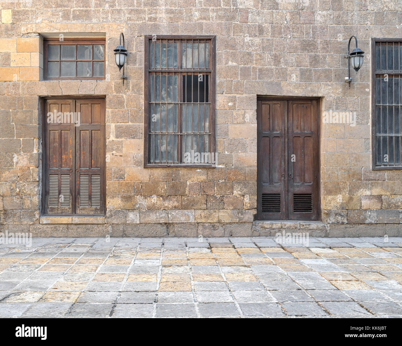 Facade of old abandoned stone bricks wall with wooden doors , windows covered with iron bars and lanterns, Cairo, - Stock Image