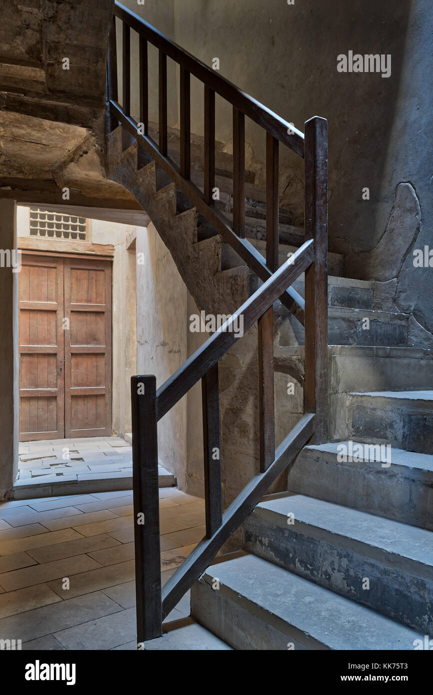 Ascending staircase with wooden balustrade and wooden closed ornate door at the background, Prince Taz palace, old - Stock Image
