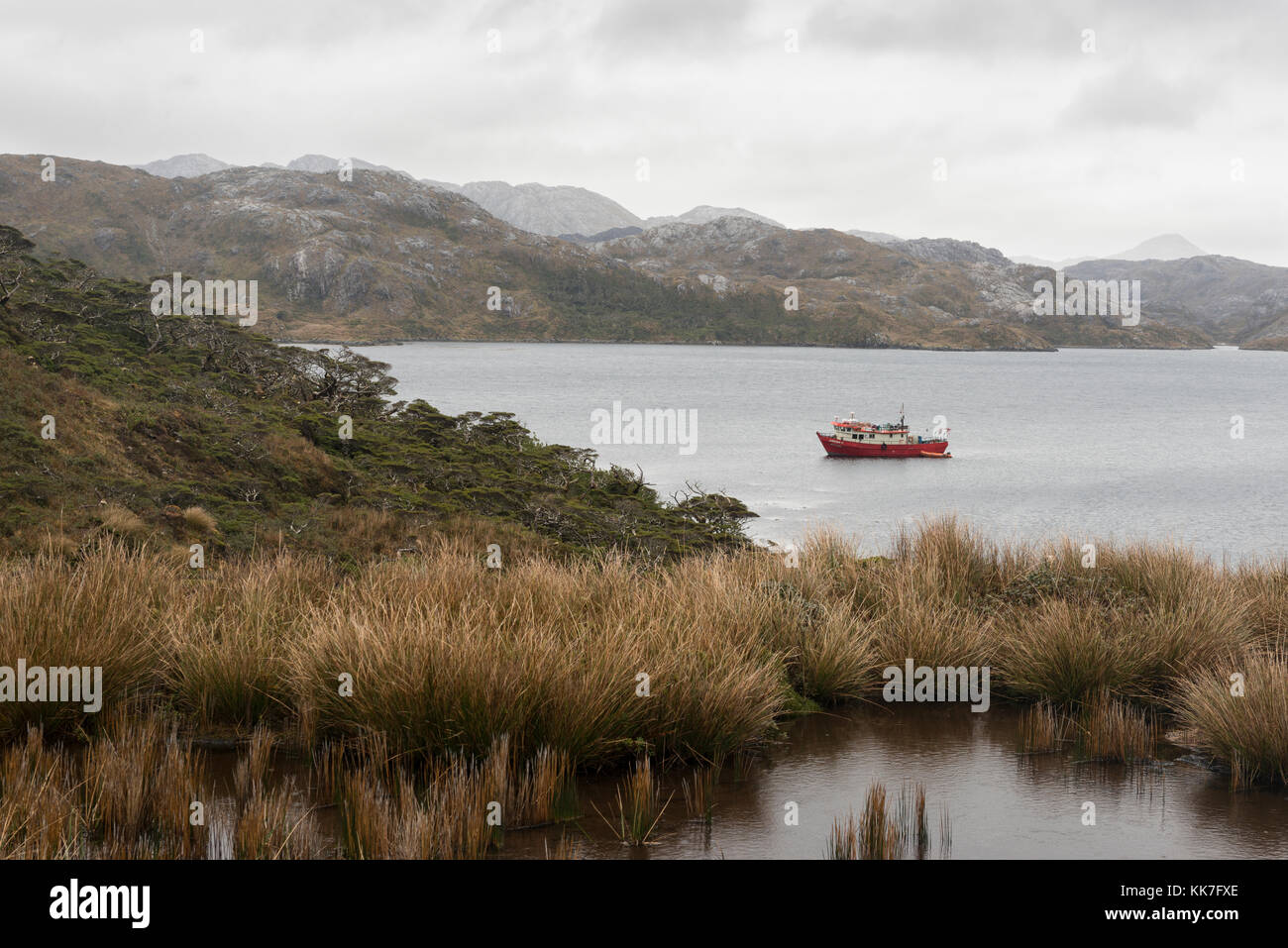 Boat moored off a remote island in southern chilean fjords - Stock Image