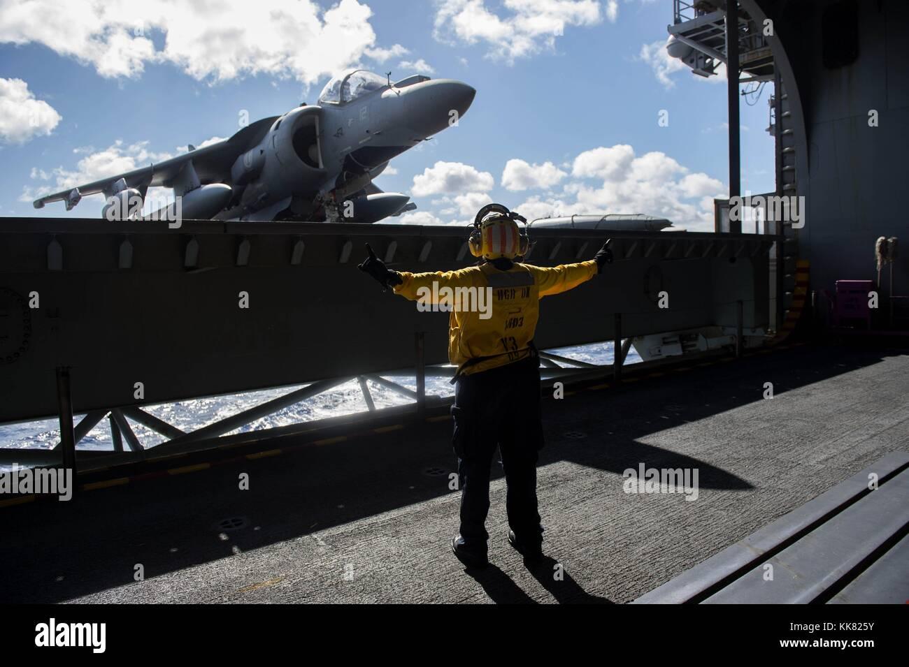 Aviation Boatswain's Mate Handling 2nd Class Araminta Mack directs an elevator operator in the hangar bay of - Stock Image