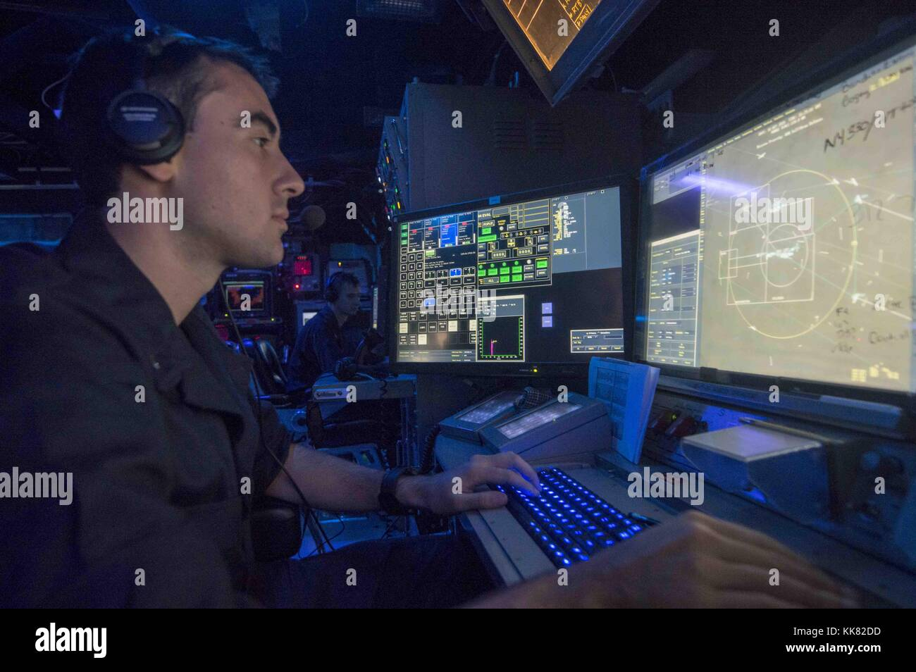 Lt jg Michael Cornish, from Omaha, Neb, stands watch in the combat information center aboard the guided-missile - Stock Image