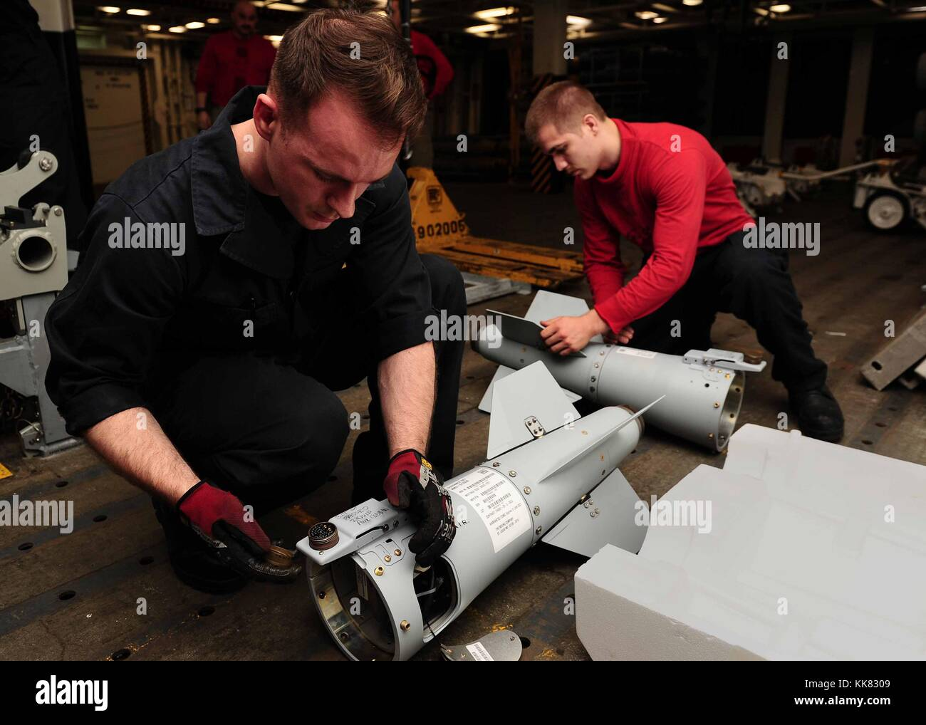 Aviation Ordnanceman Airmen Robert Perine and Nicholas Mommers inspect ordnance aboard the aircraft carrier USS - Stock Image