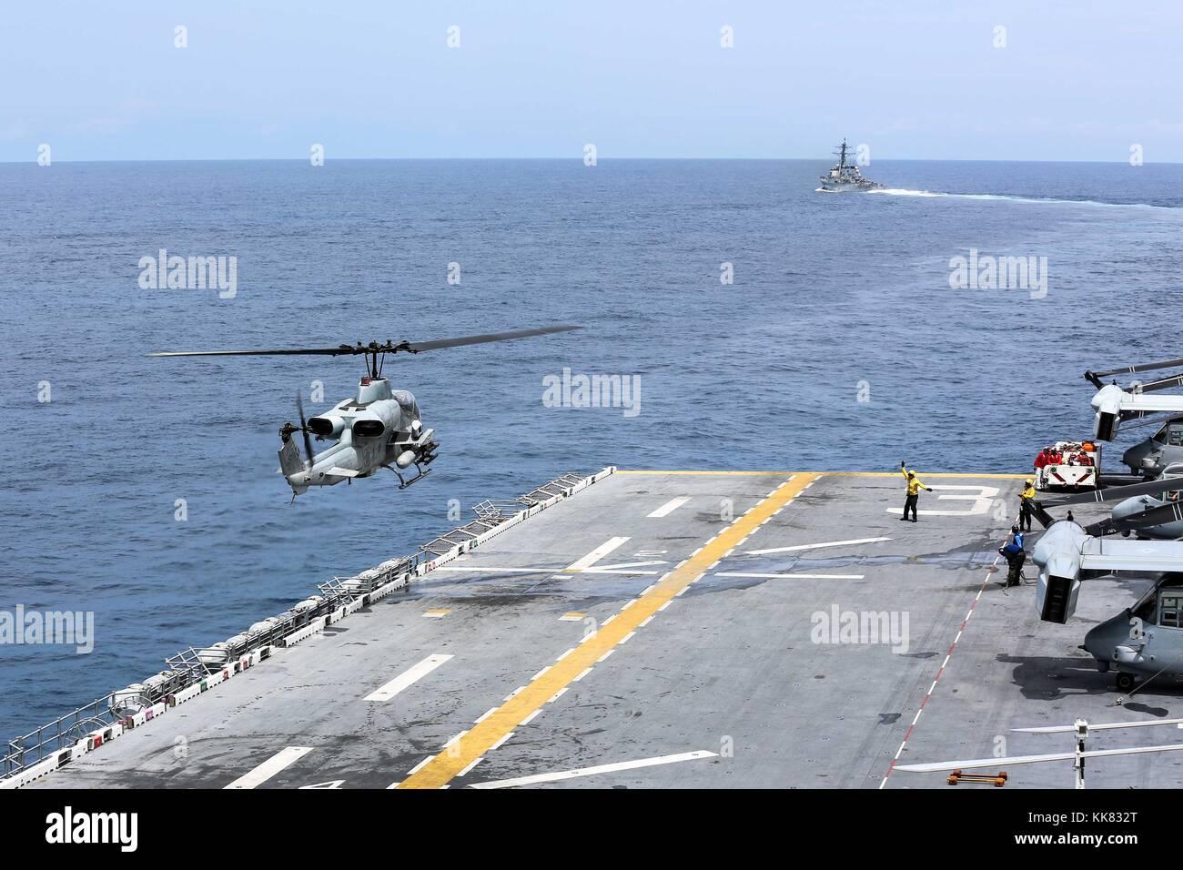 An AH-1 Cobra helicopter lands on the flight deck of the amphibious assault ship USS Kearsarge LHD 3, Atlantic Ocean. - Stock Image
