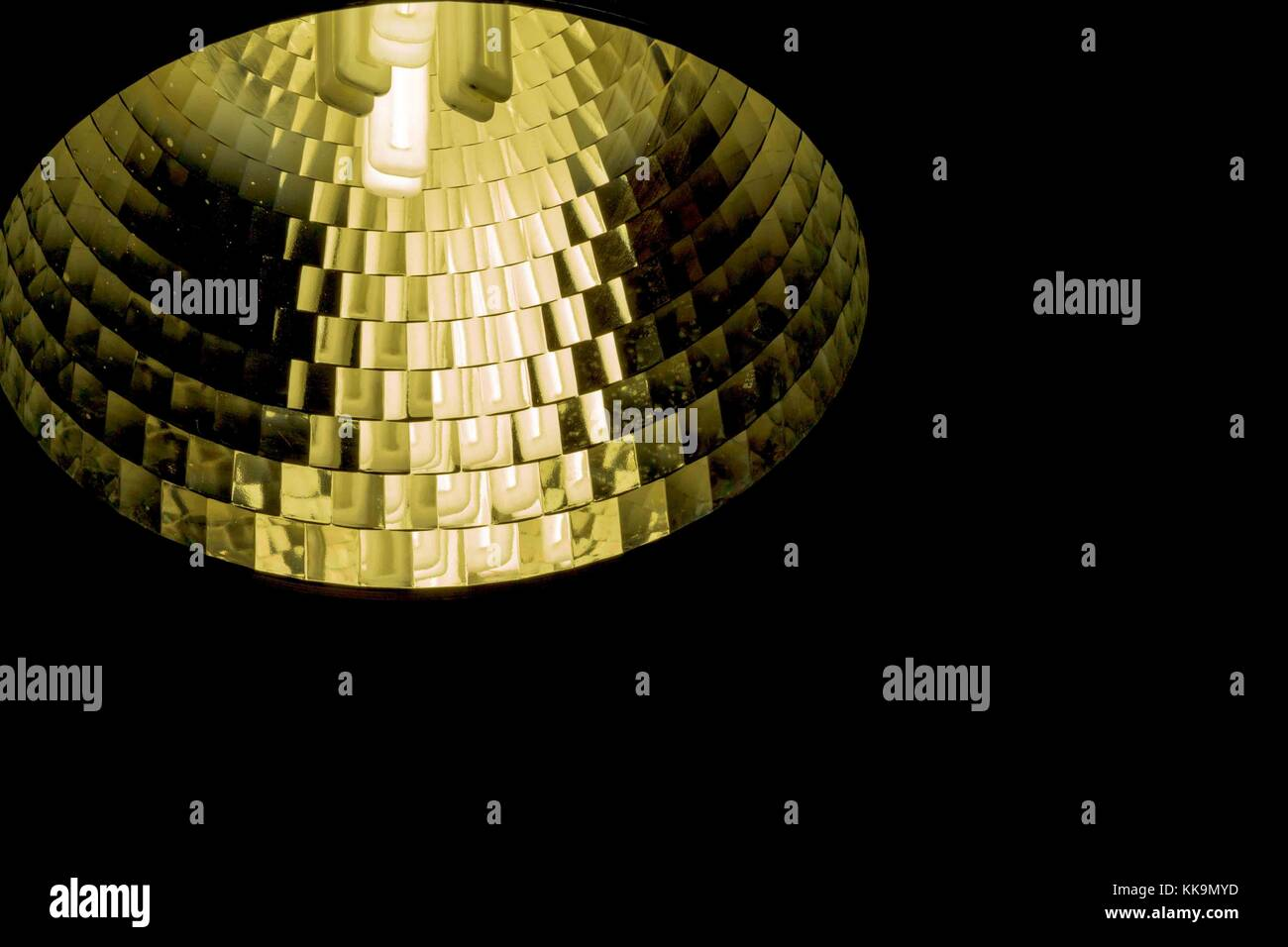 A single fluorescent light bulb spot light in a bronze yellow reflector - Stock Image