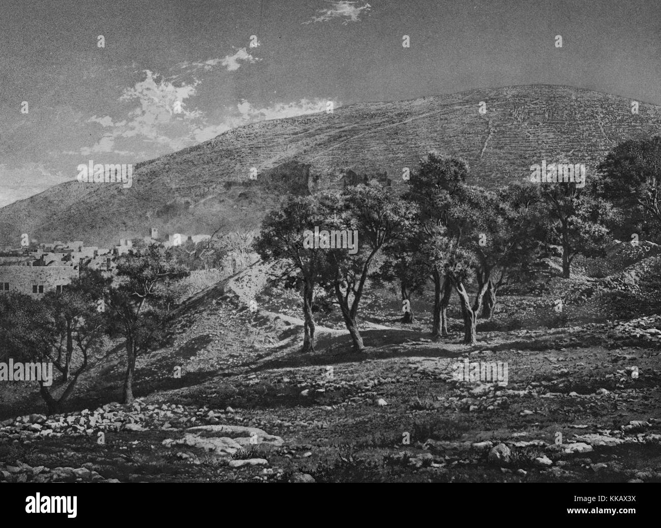Black and white photograph with rocks and trees in the foreground, hills and ancient settlement in the background, - Stock Image