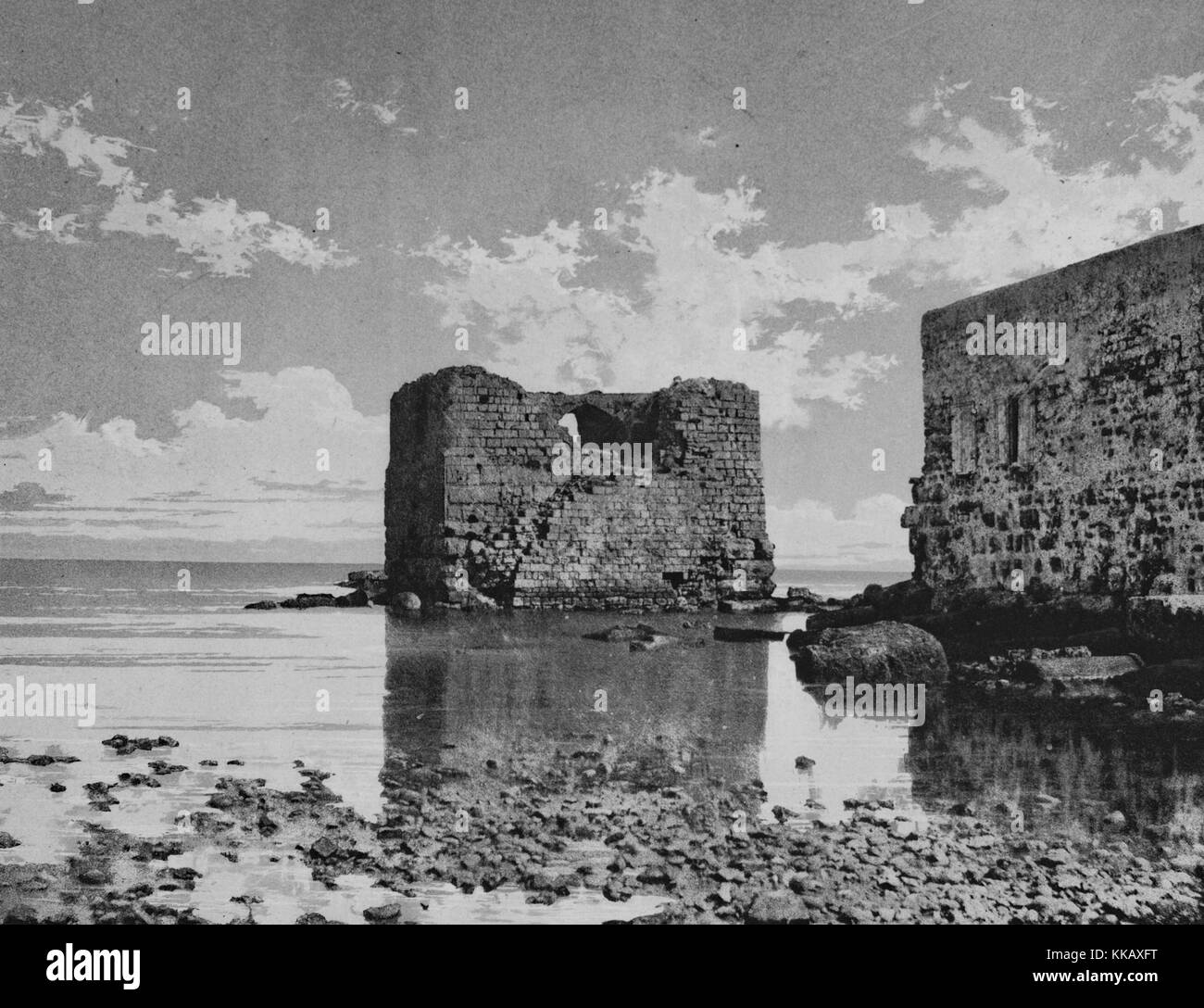 Black and white photograph of a shore, stone ruins in the shallow waters, captioned 'Tyr', Tyre, Lebanon, - Stock Image
